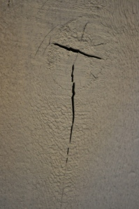 We are in the process of converting the 1970s cowboy-themed basement family room into Dave's and my bedroom (with office space for me!). When Dave painted all the rough wood, this crack-- in the shape of a cross--emerged!