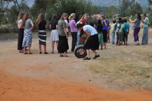 an impromptu gathering with children just outside the gates to Springs of Hope's permanent site. Notice Rachel trying to roll a tire with two sticks. She was inspired by the village boys--who were experts at it!